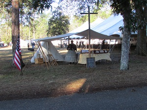 Faith standing in front of the ministry tent at the Battle of Olustee Re-enactment waith on the first group of school kids